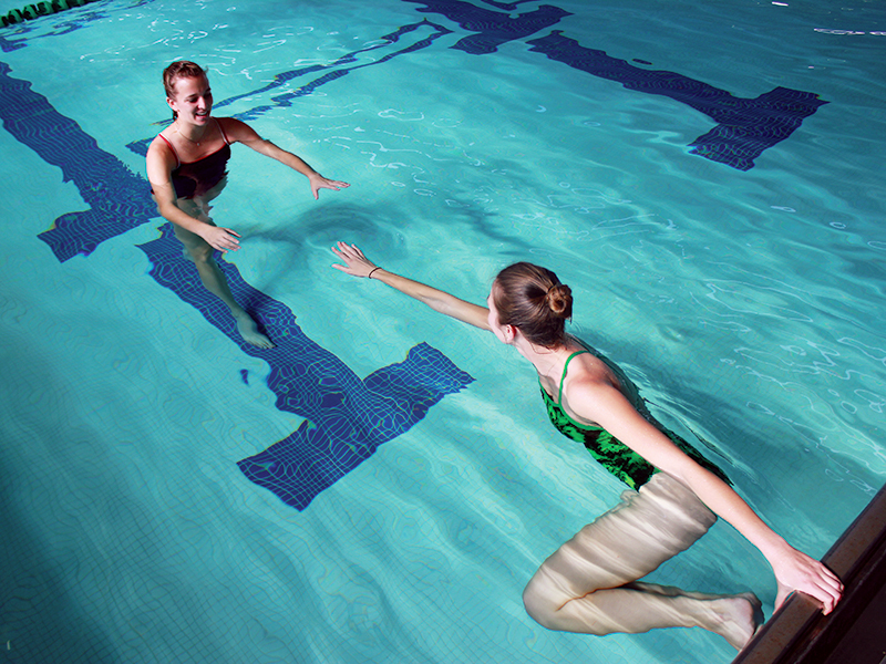 Instructor and student performing swim lessons in indoor pool