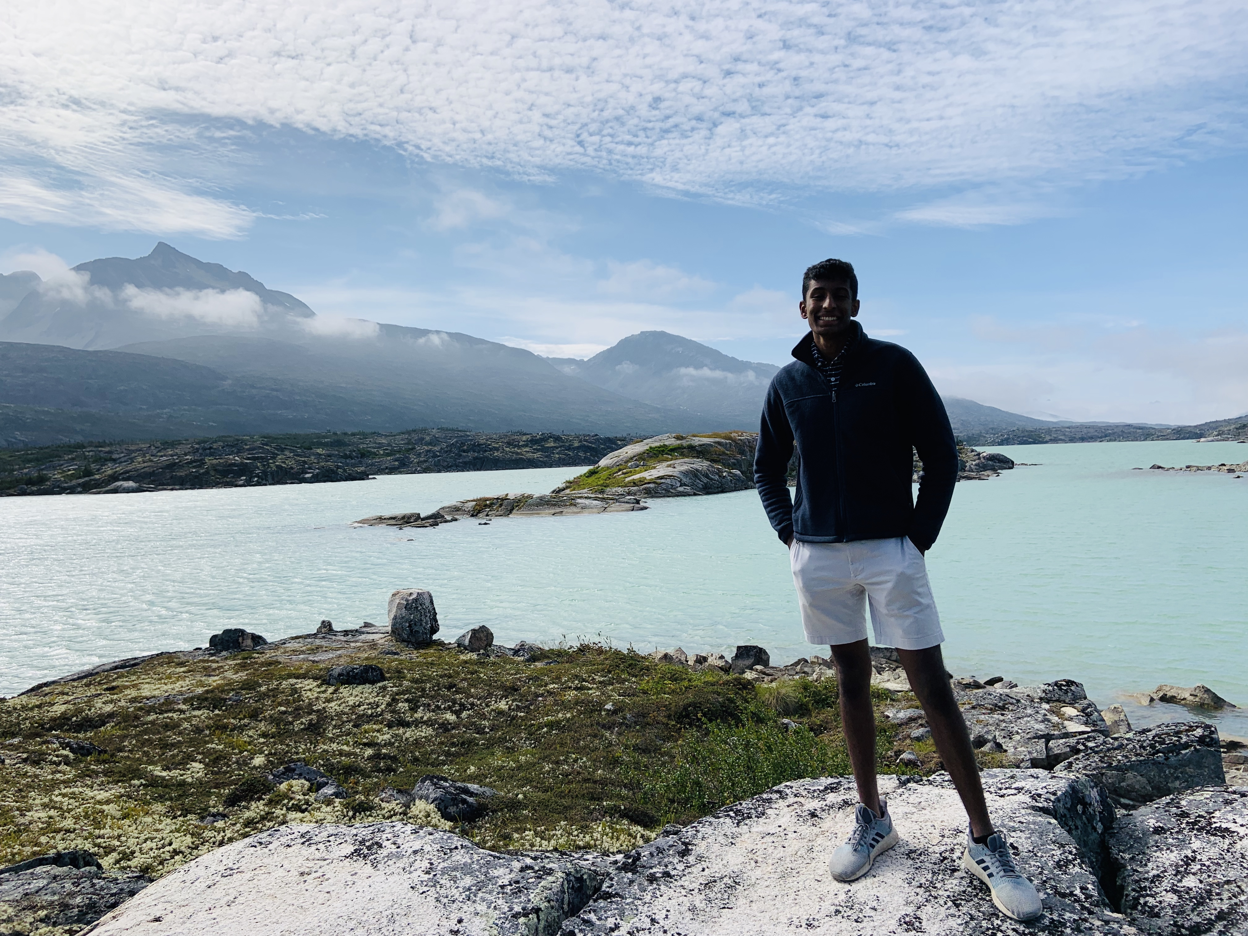 Trip Leader Sahil Inaganti standing in front of scenic mountain and ocean view