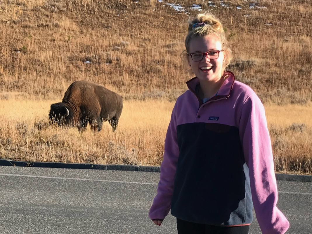 Trip Leader Lexi Sager smiling in front of a bison