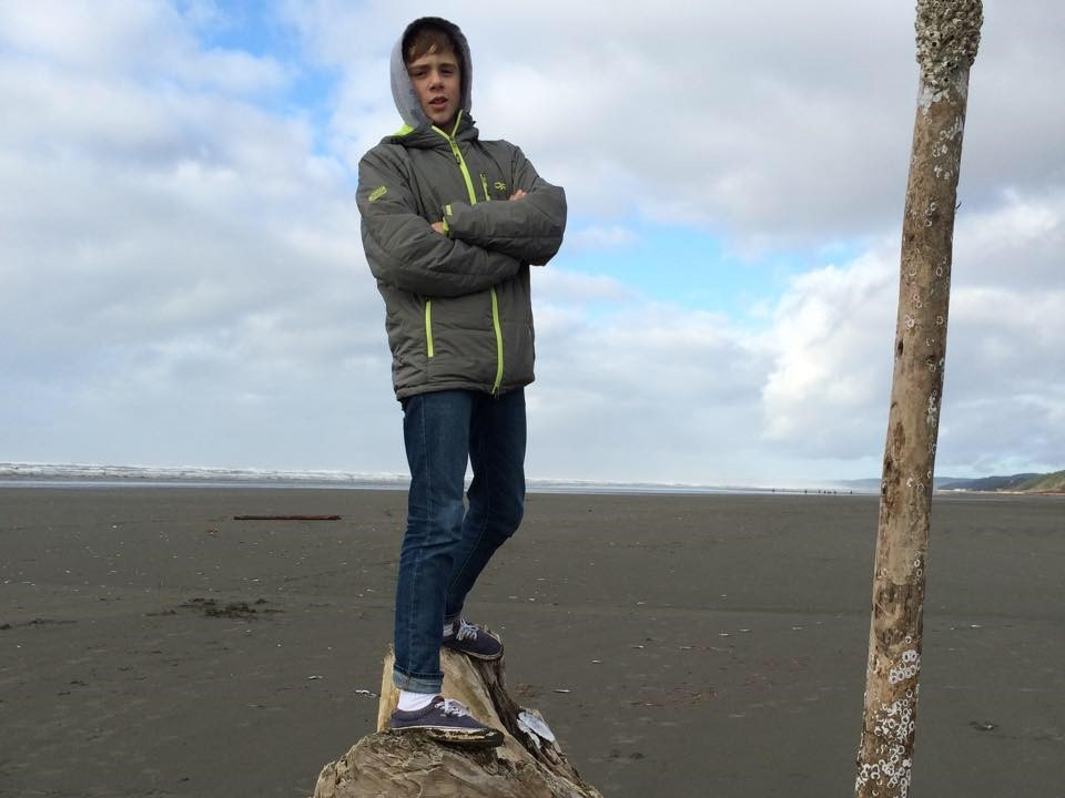 Trip Leader Asher Baden standing on a log with arms crossed