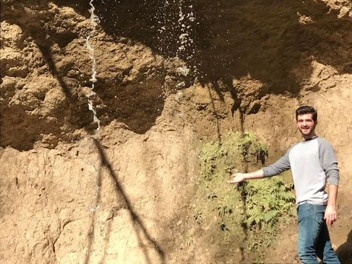 Trip Leader Ethan Faries gesturing to a stream of water coming down the side of a mountain