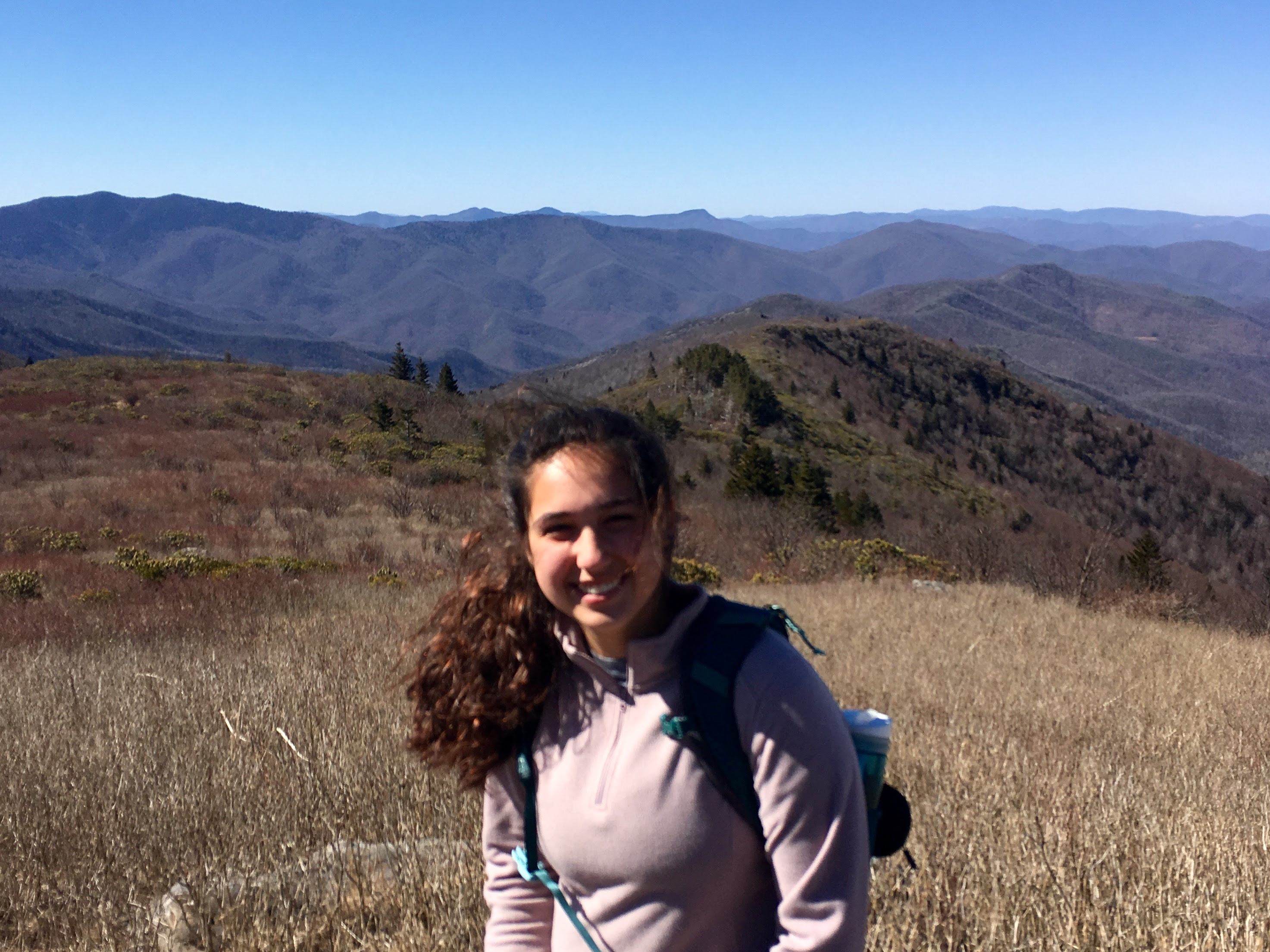 Trip Leader Lenore Alexander smiling in front of a scenic mountain view